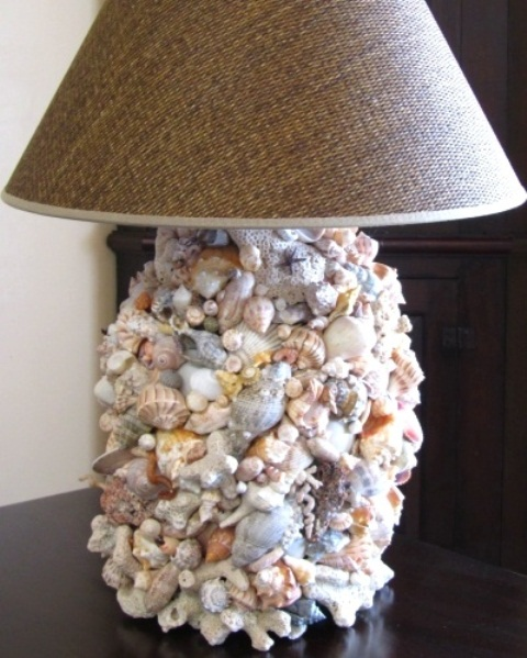 a sea-inspired table lamp with a base covered with seashells of various colors and sizes and a burlap lampshade for a rustic seaside home