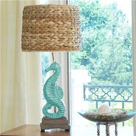 a rustic coastal table lamp with a seahorse base and a rafia lampshade is a cool idea for a beach farmhouse