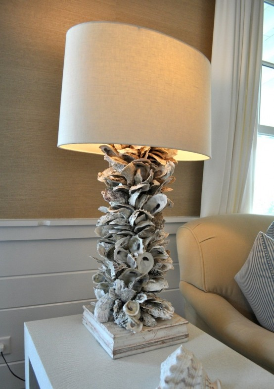 a chic table lamp with a base of seashells and a usual shade catches an eye and looks very sea-inspired