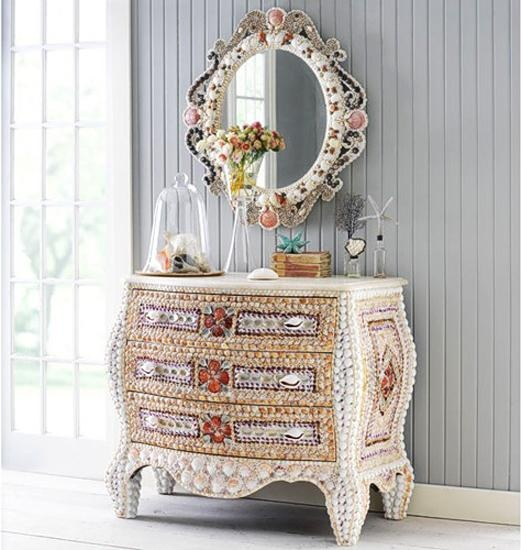 a white sideboard clad with various seashells and a matching mirror on the wall for a catchy and bold entryway of a beach home