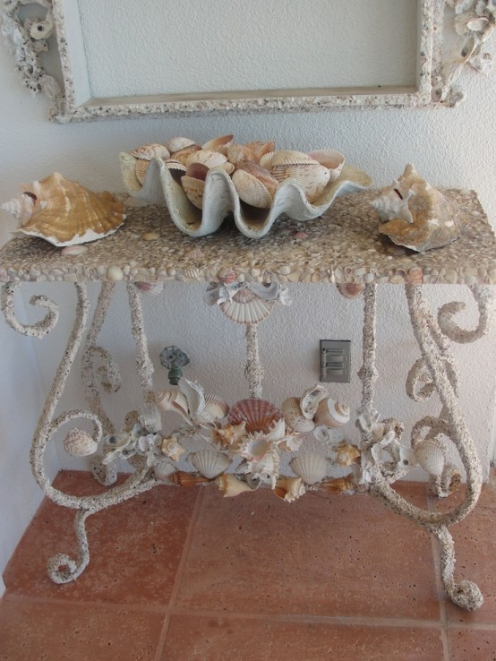 a refined sea-inspired console table with lots of seashells covering it and with seashells on top for a beach entryway