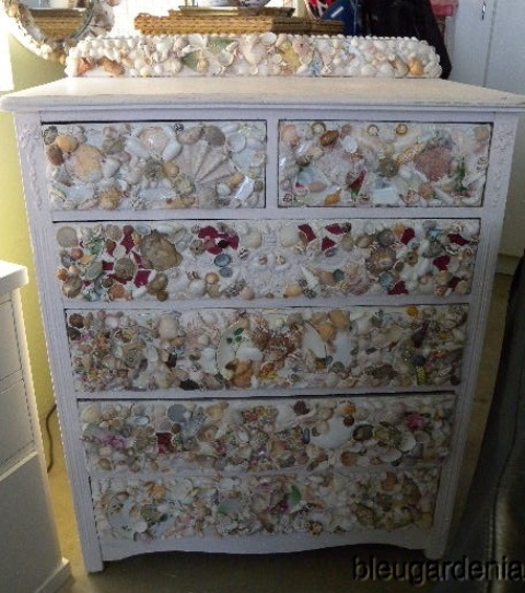 a stylish white sideboard fully clad with seashells of various kinds looks very catchy and very chic