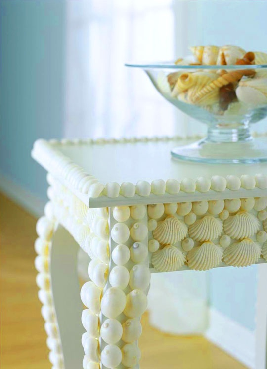 a refined vintage table clad with white seashells is a lovely idea for a beach or coastal space