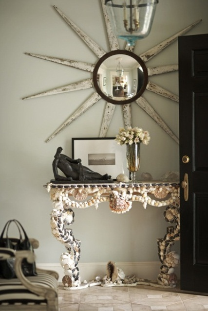 a refined vintage-inspired console table clad with seashells and pebbles looks statement-like and cool