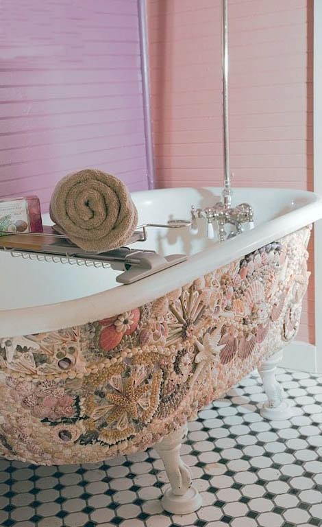 a white clawfoot tub clad with pebbles, corals and seashells looks very eye-catchy and very beautiful