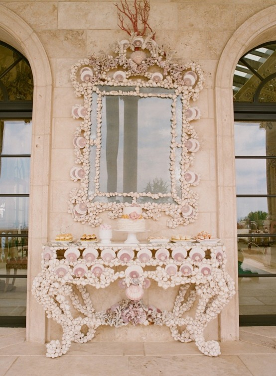 a vintage console table and a matching mirror frame fully clad with seashells of various sizes look very bold and cool