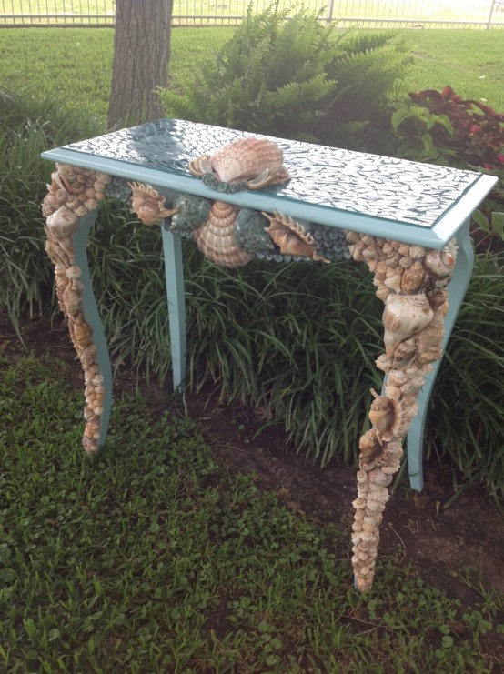 a blue vintage console table clad with seashells looks very sea-inspired and very bold
