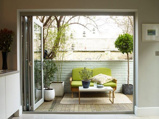 a small and cozy mid-century modern terrace with potted greenery,a  green sofa, a rug and a small coffee table