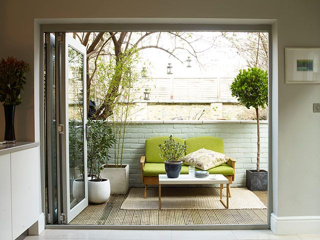 a small and cozy mid century modern terrace with potted greenery,a  green sofa, a rug and a small coffee table
