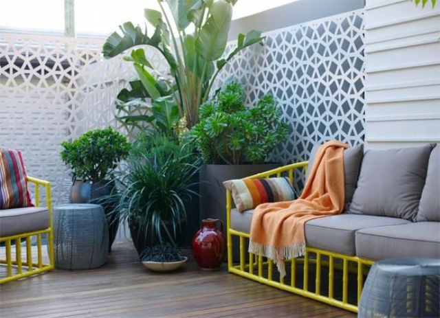 a contemporary small terrace with bright yellow furniture and grey upholstery plus lots of greenery potted