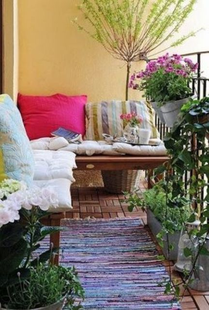 a bright boho terrace with potted blooms and greenery, a bench with colorful and patterned pillows and a rug