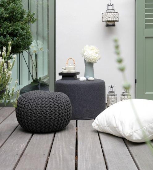a small contemporary terrace with a couple of dark ottomans and pillows, lanterns and a tea set