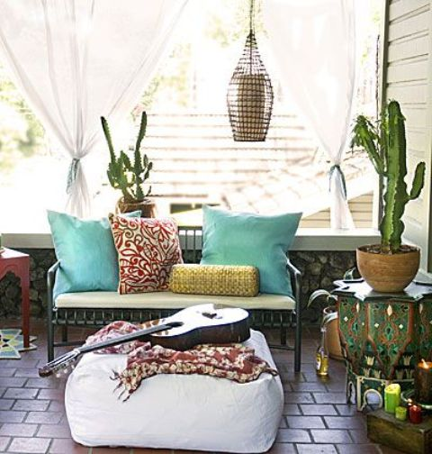 a small boho terrace with carved furniture, a white ottoman, a candle lantern and colorful textiles