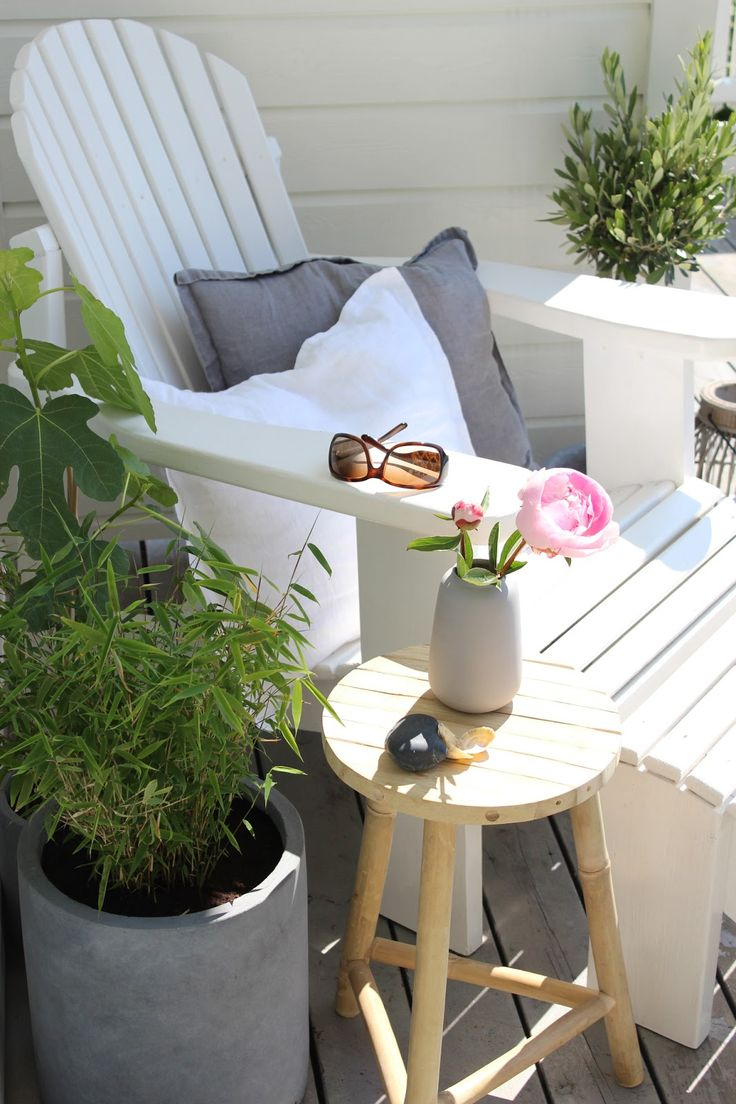 a tiny cozy terrace nook with a whiet lounger, a stool and potted greenery on the sides