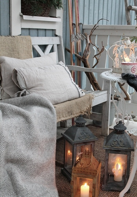 a small rustic terrace with whitewashed vintage furniture, candle lanterns, branches and skis