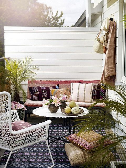 a small boho chic terrace with a bench and a chair, boho textiles and pillows plus some potted greenery