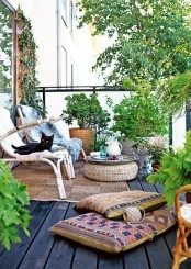 a relaxed boho terrace with rattan furniture, a wicker ottoman, boho pillows, potted greenery and blooms
