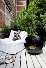 a small contemporary terrace with a black hearth, a white lounger and much greenery for freshness and privacy