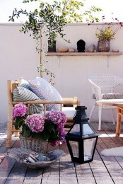 a tiny eclectic terrace with rattan and wicker furniture, candle lanterns and potted greenery and blooms