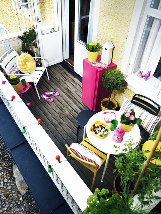 a small colorful terrace with simple bright furniture, colorful and striped textiles, storage units and potted greenery and blooms