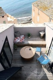 a small terrace with a beach view, blue chairs, a wicker table and a bright pillow plus a smaller one