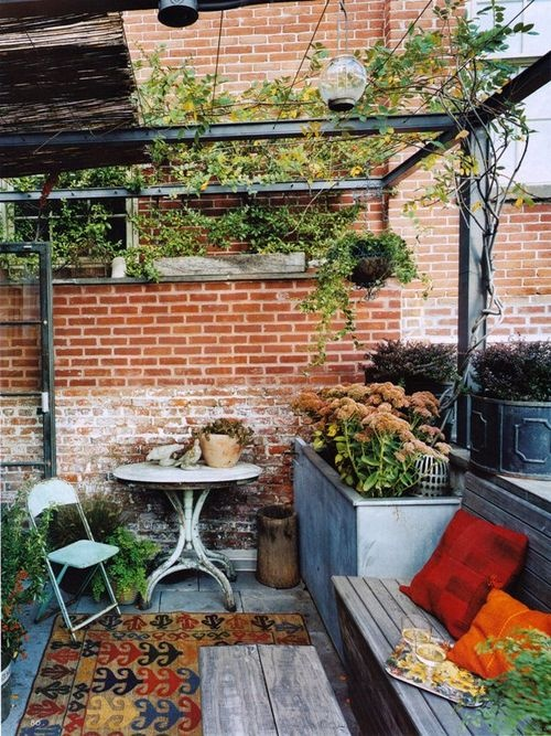 a small shabby chic terrace with rustic and vintage furniture, boho rugs and potted greenery and blooms