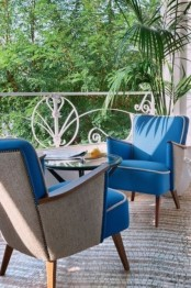 an elegant small terrace with blue upholstered chairs, a rug and a glass coffee table