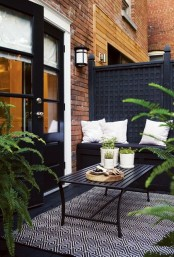 a moody small terrace with black furniture, rugs and lots of potted greenery to refresh the space