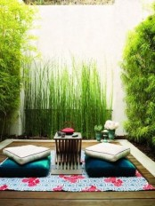a small zen terrace with a rug, cushions and a tiny coffee table and lots of greenery and bamboo around