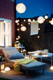 a small terrace with comfy contemporary furniture, lights, blooms and greenery in pots