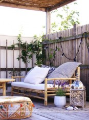 a small boho terrace with candle lanterns, rattan furniture, potted greenery and blooms plus lights