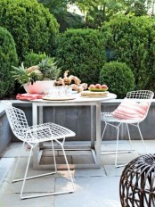 a small contemporary terrace with an eating space, wire chairs, a metal and wood table and a rattan ottoman