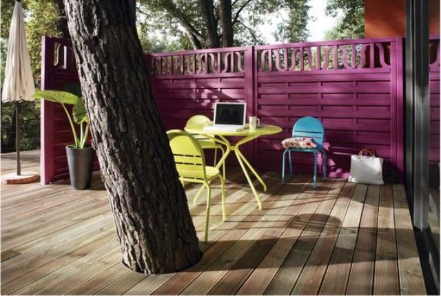 a small bright terrace with a fuchsia wall, bright yellow furniture, a blue chair and a comfy working space