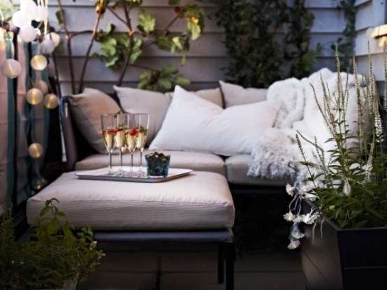 a small contemporary terrace with potted greenery, neutral upholstered furniture and lights
