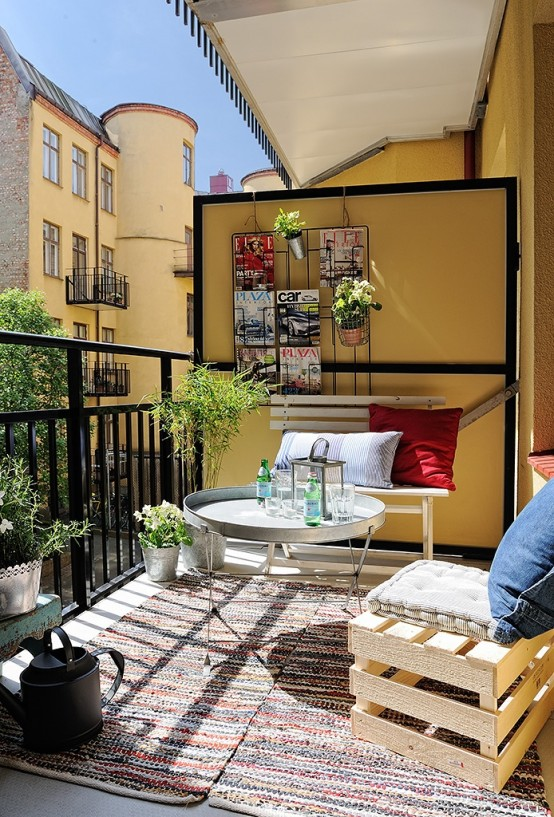 a small terrace with crate and metal furniture, rugs, potted greenery and a grid with some magazines and plants
