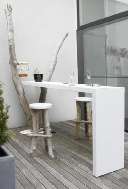 a small minimalist terrace with an old tree and a sleek white countertop that can be used as a bar counter or a desk