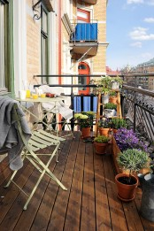 lots of greenery and bright blooms in wooden and terra cotta pots will make your balcony feel like spring and a bit rustic