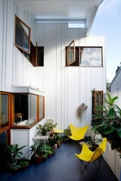 lots of potted greenery and sunny yellow chairs will make your balcony fresh and inviting