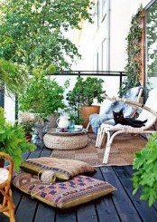 lots of greeneryin baskets, boho rugs and cushions, jute rugs and ottomans and a rattan chair for a boho feel