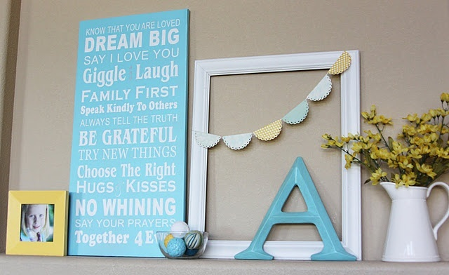 a bright summer mantel in blue and yellow, with a blue sign, a letter, pastel garland and a family photo