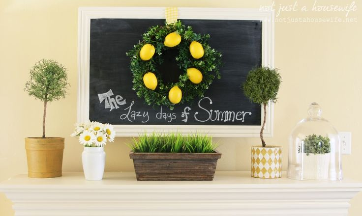 a traditional summer mantel with a chalkboard, a lemon wreath, potted blooms and greenery and a box with grass