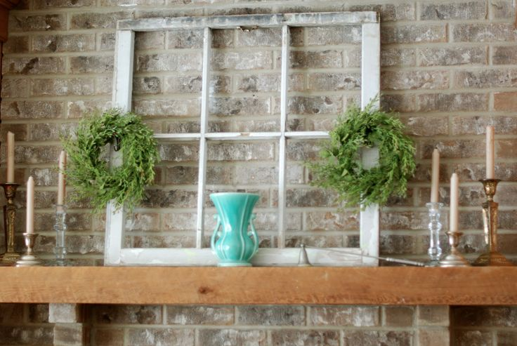 a simple rustic summer mantel with a vintage window, greenery wreaths, candles and a turquoise vase