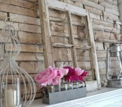 a summer mantel with a vintage window, candle lanterns, an arrangement of bright pink blooms