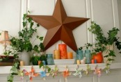 a bright summer mantel with a star, potted greenery, colorful candles and jars plus a paper banner