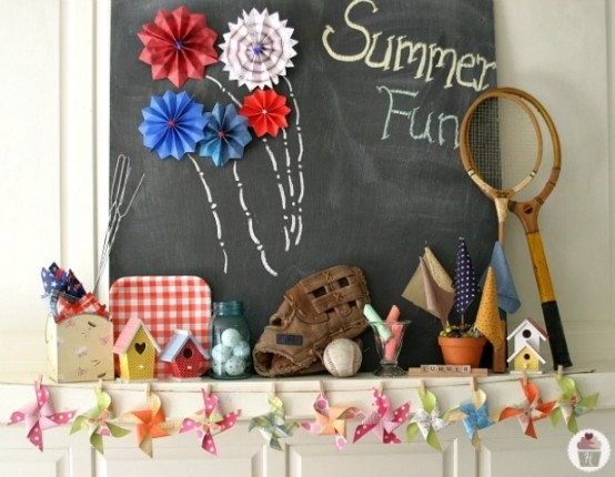 a summer fun mantel with a chalkboard, bird houses, planters, jars, baseball items and a colorful garland