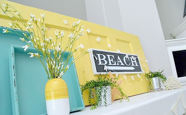 a colorful summer mantel in turquoise and yellow, with potted greenery, a sign and blooming branches