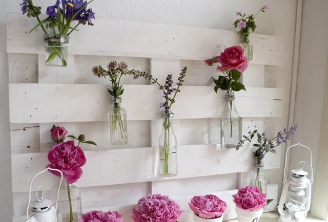 a blooming summer mantel with a white pallet, bright pink blooms and white candle lanterns