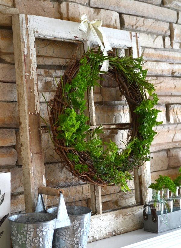 a rustic summer mantel with a shabby chic window, a greenery wreath, metal buckets and greenery in vases