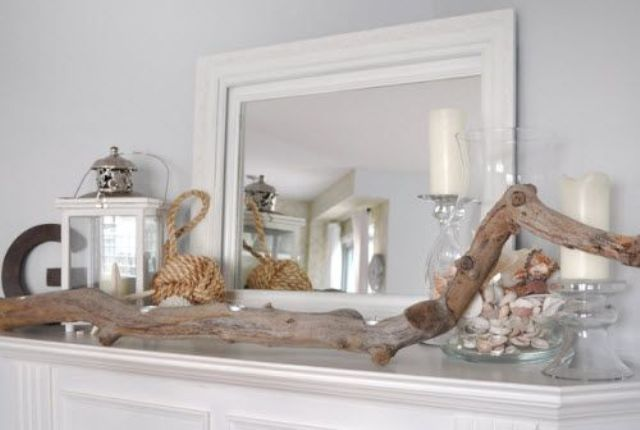 a beachy summer mantel with candles, lanterns, driftwood, rope and a large jar with shells
