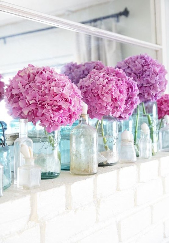 a bright summer mantel with bright pink hydrangeas in vases, seashells in jars